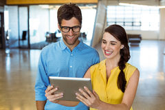 Business executive and co-worker looking at digital tablet. In office Stock Photography
