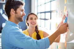 Business executive and co-worker putting sticky notes on whiteboard Royalty Free Stock Image