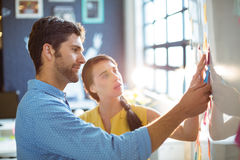 Business executive and co-worker putting sticky notes on whiteboard Stock Image