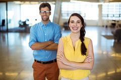 Business executive and co-worker standing with arms crossed Stock Photo