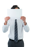 Business executive covering his face behind blank paper Stock Photos