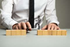 Business executive drawing a line for a silhouetted businessman stock image