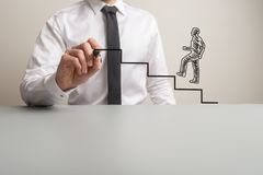 Business executive drawing steps for a handdrawn businessman to climb royalty free stock image