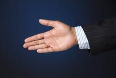 Business executive extending arm to shake hands. Corporate businessman raising arm to shake hands Stock Photo