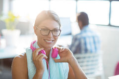 Business executive holding headphones in office Royalty Free Stock Image