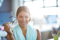 Business executive holding spectacles in office Royalty Free Stock Image