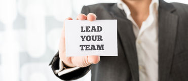 Business executive holding up a white card with a Lead your team Royalty Free Stock Photography