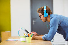 Business executive listening to music on digital tablet Stock Photography