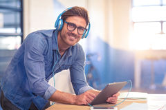 Business executive listening to music on digital tablet Stock Images