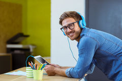 Business executive listening to music on digital tablet Royalty Free Stock Images
