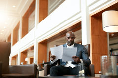 Business executive at lobby reading documents Royalty Free Stock Images