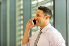 Business executive on mobile phone. Happy business executive talking on mobile phone in office Royalty Free Stock Photography
