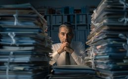 Business executive overloaded with work. Stressed exhausted business executive working in the office late at night with piles of paperwork, he is overloaded with royalty free stock photography