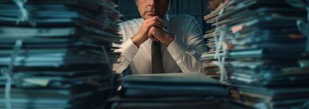 Business executive overloaded with work. Stressed exhausted business executive working in the office late at night with piles of paperwork, he is overloaded with stock photos
