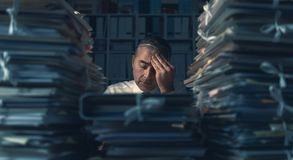 Business executive overloaded with work. Stressed exhausted business executive working in the office late at night with piles of paperwork, he is overloaded with royalty free stock photo