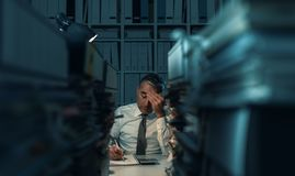 Business executive overloaded with work. Stressed exhausted business executive working in the office late at night with piles of paperwork, he is overloaded with stock photography