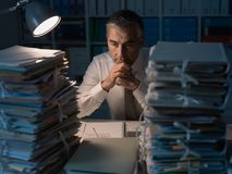 Business executive overloaded with work. Stressed exhausted business executive working in the office late at night with stacks of paperwork, he is overloaded stock photography