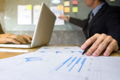 Business executive pointing graph presentation to colleagues in stock photography