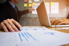 Business executive pointing graph presentation to colleagues in Royalty Free Stock Images