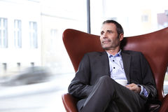 Business executive in red chair enjoying coffee. Stock Photos