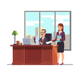 Business executive with a secretary at his desk Royalty Free Stock Photo