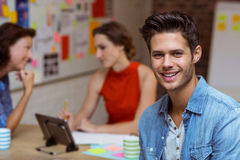 Business executive smiling and colleagues discussing in background Royalty Free Stock Photos