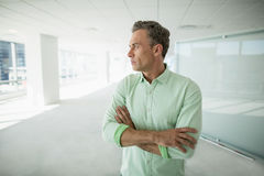 Business executive standing with arms crossed in office corridor Stock Photo