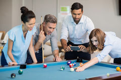 Business executive taking picture with mobile phone while colleagues playing pool Royalty Free Stock Photo