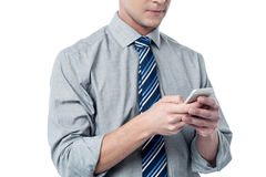 Business executive using cell phone. Young corporate man texting thru his smart phone Royalty Free Stock Photo