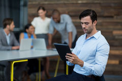 Business executive using digital tablet in office. Attentive business executive using digital tablet in office Royalty Free Stock Photos