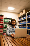 Business executive using laptop in file storage room Stock Photos