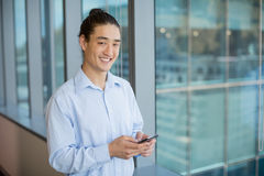 Business executive using on mobile phone in corridor Royalty Free Stock Photos