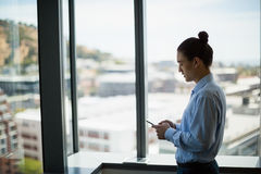 Business executive using on mobile phone in corridor Royalty Free Stock Photo