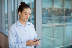 Business executive using on mobile phone in corridor Stock Photography