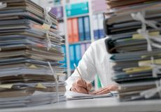 Businessman working in the office and piles of paperwork. Business executive working in the office and piles of paperwork, he is overloaded with work stock photo