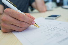 Business executive writing on a document. Close-up of business executive writing on a document at his desk in office Royalty Free Stock Image