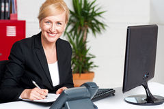 Business executive writing her appointments stock photography