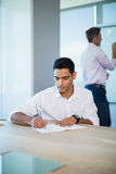 Business executive writing on notebook in conference room Royalty Free Stock Photography