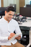Business executive writing on notebook in office Stock Photo