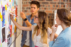 Business executive writing on sticky notes on whiteboard Stock Photos