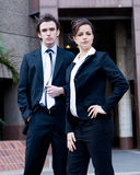 Business executives. Two beautiful young business man and woman executives standing outside office, background is a blue glass corporate building stock photo