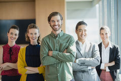 Business executives with arms crossed smiling while standing in office. Portrait of business executives with arms crossed smiling while standing in office Royalty Free Stock Images