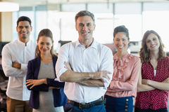 Business executives with arms crossed smiling while standing in office. Portrait of business executives with arms crossed smiling while standing in office Royalty Free Stock Image