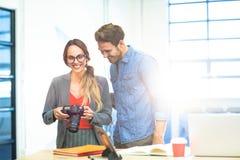Business executives checking photos in camera Stock Photos