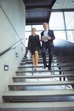 Business executives climbing down the stairs. At office Royalty Free Stock Photos