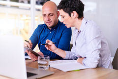 Business executives collaborating together using technology to make progress. Caucasian male and female business partners working together in the conference room royalty free stock image