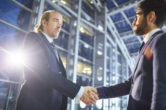Business executives congratulating each other. Serious confident multi-ethnic business executives in formal suits making handshake while congratulating each stock photo