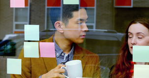Business executives discussing over sticky notes stock footage