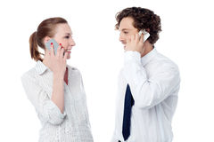 Business executives engaged over a phone call. Young colleagues communicating over cell phone stock image