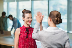Business executives giving high five to each other. In office stock photography